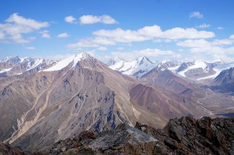 Вид с Турана на восток - слева, вдали горы Малоалматинского отрога, за ними виден пик Талгар. На переднем плане пик Советов (4240 м), далее направо - Советских альпинистов (4379 м), Молодая Гвардия (4398 м), Искра (4228 м), Олега Кошевого (4262 м)